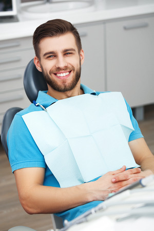 toothcare: My smile is perfect! Portrait of happy patient in dental chair. Stock Photo
