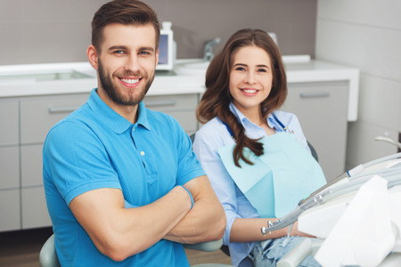 Portrait of a male dentist and young happy  female patient in a dentist office.