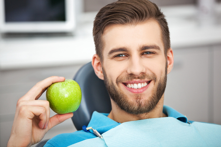 dentist: Mi sonrisa es perfecta! Retrato del paciente feliz en silla dental con manzana verde.