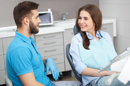 young male: Portrait of a male dentist and young happy  female patient in a dentist office.