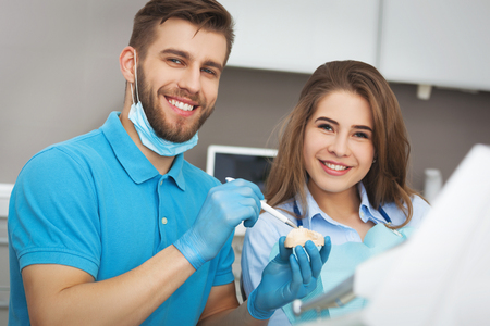 dentist and patient: Shot of a male dentist explaining  to young female patient how to properly brush her teeth.
