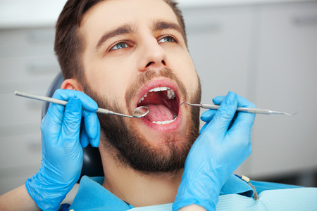 Shot of a young man getting his teeth checked by a dentist.