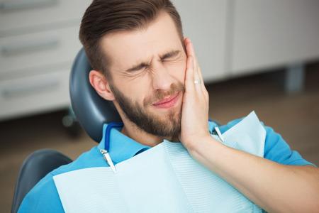 Shot von einem jungen Mann mit Zahnschmerzen, während in einem Zahnarztstuhl sitzen.