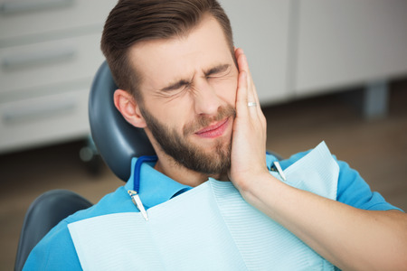 toothcare: Shot of a young man with tooth pain while sitting in a dentists chair. Stock Photo