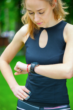rate: Female runner looking at her sport watch. Measuring heart rate.