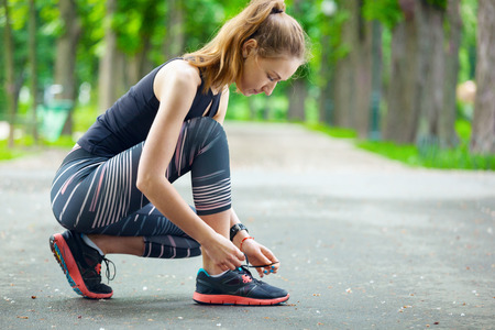 Shot of a beautiful young woman tying her laces before a run.