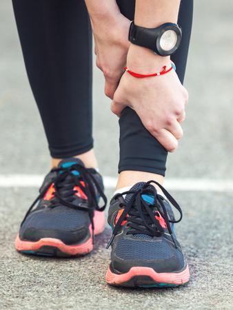 splint: femenino joven del corredor es la celebración de su pierna lesionada. problema de calambres en la pierna.
