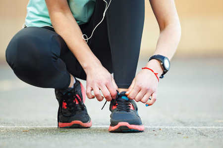 preparation: Close up of young woman tying her laces before a run. Stock Photo