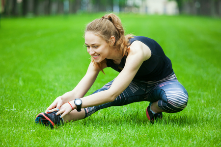 green park: Full length shot of an attractive young woman stretching before running.