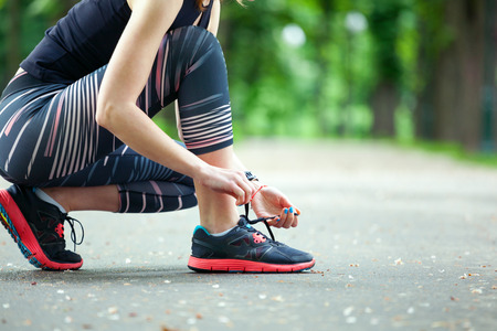girl shoes: Close up of young woman tying her laces before a run. Stock Photo