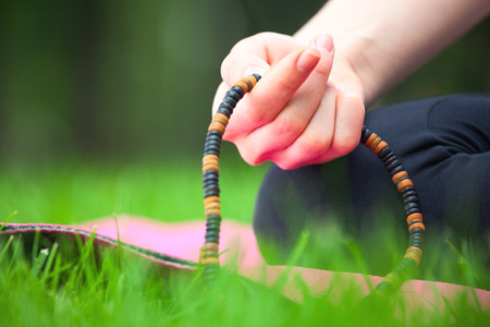 tibetian: Close up of female hand holding rosary - meditation concept.