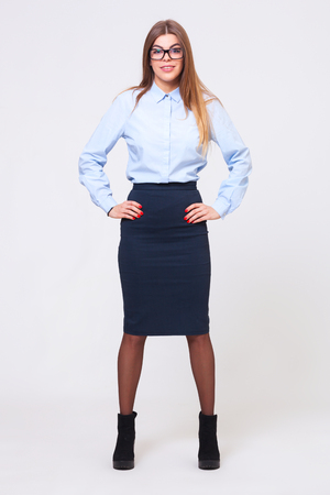 full shot: Full body studio shot of young beautiful business woman isolated on gray background.