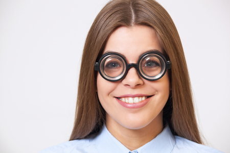 Studio portrait of funny happy  young business woman in big nerd eyeglasses on gray background.