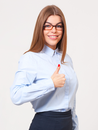 alright: Everything is alright! Young beautiful business woman showing thumbs up sign isolated on gray background.