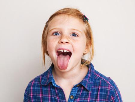 Happy redhead mała dziewczynka w niebieskiej koszuli kratę pokazano jej język.