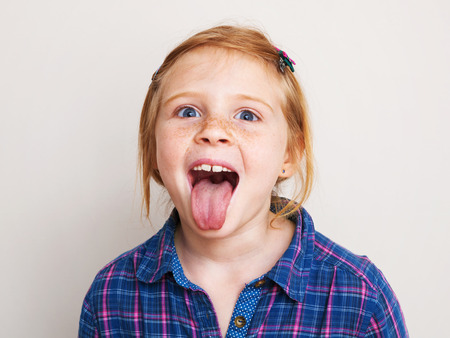 Niña pelirroja feliz en camisa a cuadros azul mostrando su lengua.