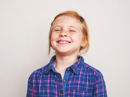 Portrait of happy redhead little girl in blue plaid shirt smiling. photo