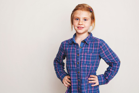 Portrait of little redhead girl in blue plaid shirt posing against wall. photo