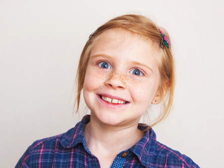 Portrait of funny redhead little girl smiling against wall. photo