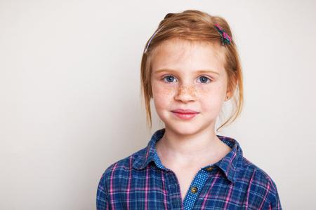 Redhead little girl in blue plaid shirt posing against wall. photo