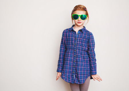 Redhead little girl in green sunglasses and blue shirt posing against wall. photo