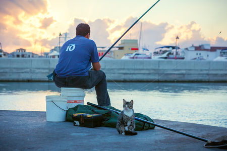 CYPRUS, LIMASSOL - SEPTEMBER 22 2016: Local with cat fishing in the Limassol Old Port at sunset. Фото со стока - 81986679