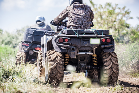 Back view of quad bike  zipping along a country road. Stock Photo