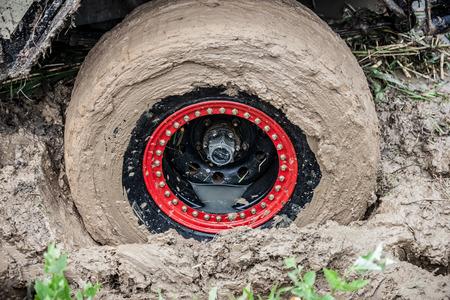 Off road car stuck in deep mud. Wheel close up. Stock Photo