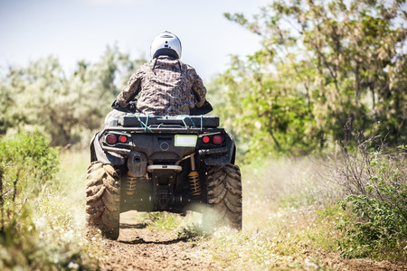 Back view of quad bike  zipping along a country road. 스톡 콘텐츠