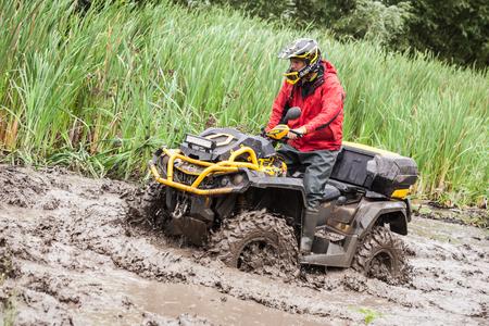 LUBOTIN, UKRAINE - JULY 23, 2016: RFC Ukraine Wild Boar Challenge 2016. The participant on quad bike passes a deep water pit.