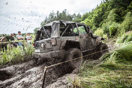 LUBOTIN, UKRAINE - JULY 23, 2016: RFC Ukraine Wild Boar Challenge 2016. The participant on Jeep passes a deep muddy pit.