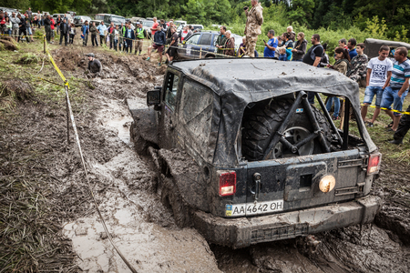 LUBOTIN, UKRAINE - JULY 23, 2016: RFC Ukraine Wild Boar Challenge 2016. The participant on Jeep passes a deep muddy pit.