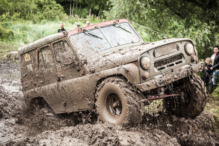 LUBOTIN, UKRAINE - JULY 23, 2016: RFC Ukraine Wild Boar Challenge 2016. Custom built Off-road Trophy UAZ 469 passing mud pit. Editorial
