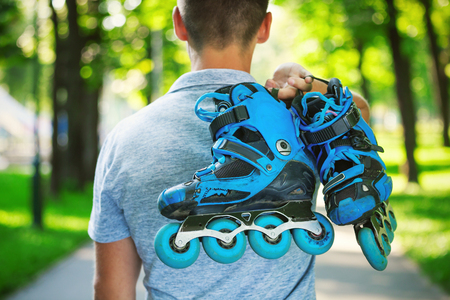 Young male roller skater holding inline roller skates. Shoot from behind. Stock Photo