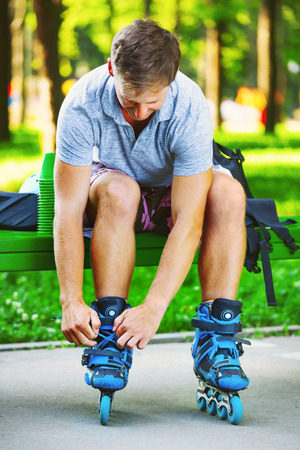 Young handsome guy tying laces on his inline roller skates. Stock Photo