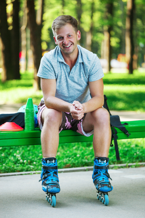 Portrait of happy handsome male roller in inline roller skates sitting on bench on the park. Stock Photo