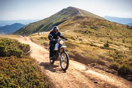 Group of enduro bikers cross road at high speed in Carpathian mountains. Ukraine.