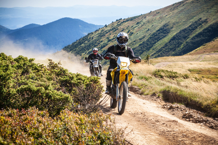 Group of enduro bikers cross road at high speed in Carpathian mountains. Ukraine.
