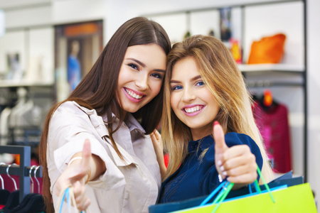 Beautiful young women with shopping bags looking happy and showing thumbs up.