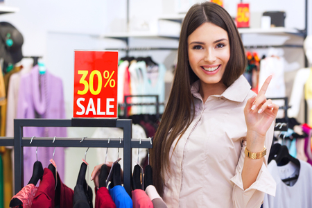 Portrait of beautiful young happy woman with red sale sign in a clothing store.
