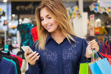 Beautiful woman with shopping bags looking at her phone while going out on a shopping spree. Stock Photo