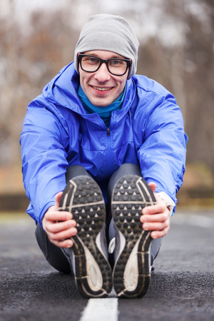 Shot of a young handsome professional runner stretching outdoors.