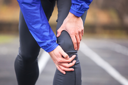 Cropped shot of a young man holding his knee in pain while running.