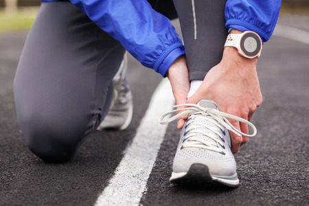 Cropped shot of a young runner holding his ankle in pain.