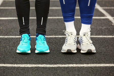 Front view of two runners in running shoes standing.