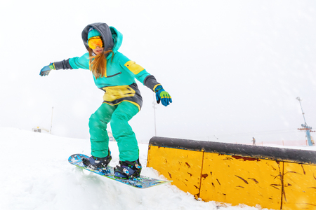 Portrait of young snowboarder jumping on ramp.