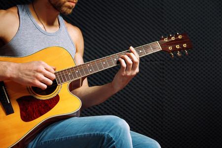 Handsome rock guitarist practicing in sound studio. Stock Photo
