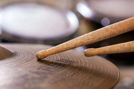 Close up of a pair of drumsticks lying on cymbal.