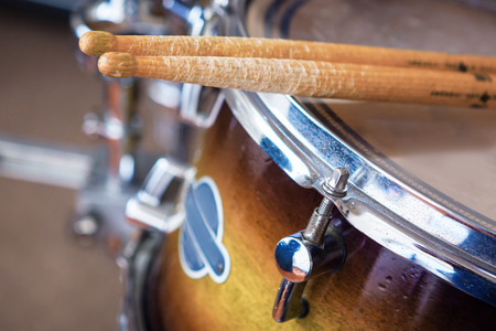 Close up of a pair of drumsticks lying on tom-tom drum. Stock Photo