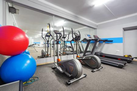 Cardio zone in modern gym. Ellipticals and treadmills.